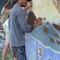 Pandji painting baby turtles at Taima