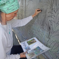 Mural Artist Sandra Noel using charcoal on Teku/Toweer Mural