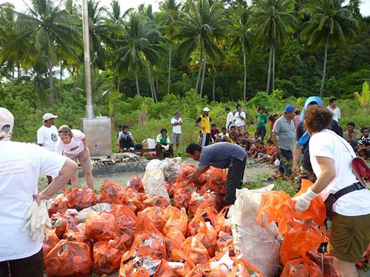 Villagers and AlTo eco-service travelers pick up trash for disposal in Teku's new incinerator
