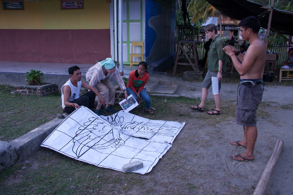Ipan, Sandra and Agus using charcoal paper to outline large animals
