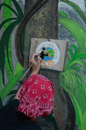 Sandra painting AlTo sign on Teku/Toweer Mural