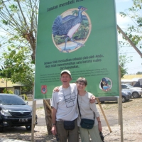 Will Forrester and Rayna Holtz in front of Maleo bird billboard at airport