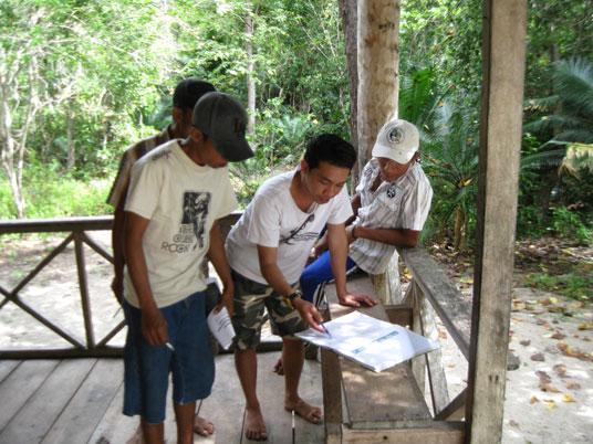 Conservation Officer AlTo Ipan melatih beberapa petugas desa yang baru bagaimana menjaga dan mencatat data burung maleo.
