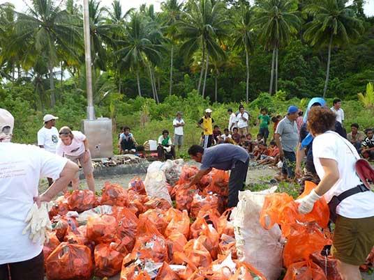 Orang desa dan pengunjung eko-wisata mengumpulkan sampah untuk dibakar dalam insineratur yang baru di Teku.
