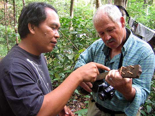 with help of a new friend, visitor plays Indonesian stringed instrument